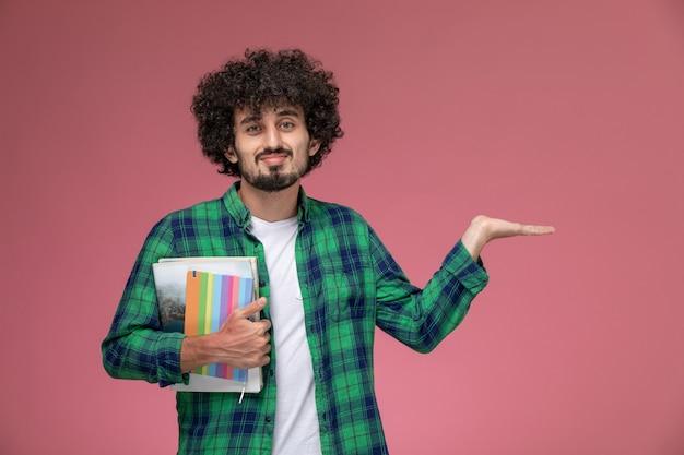 Widok z przodu młody człowiek pokazuje pustą rękę z notebookami