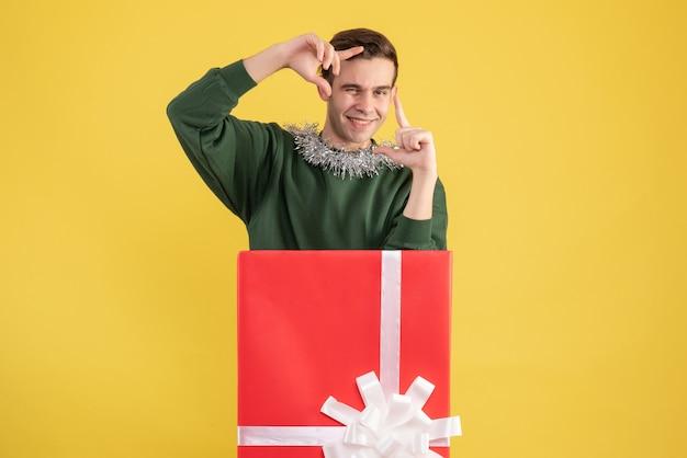 Widok z przodu młody człowiek robi aparat znak stojący za dużym pudełkiem na prezent na żółto