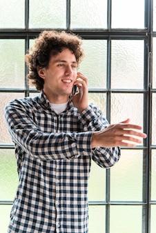 Widok z przodu młody człowiek rozmawia przez telefon