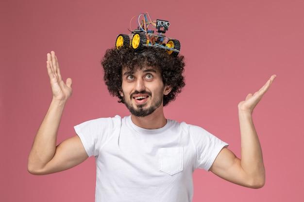 Widok z przodu młody człowiek stawiając jego innowację robota na głowie