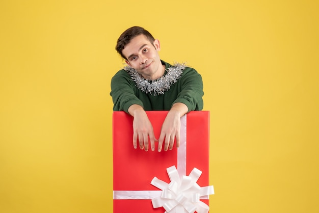 Widok z przodu młody człowiek stojący za dużym pudełkiem na prezent na żółto