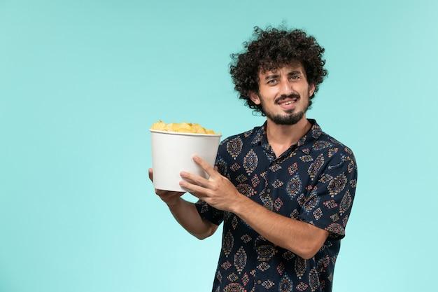 Widok z przodu młody człowiek trzyma kipsy ziemniaczane na jasnoniebieskim biurku kino męskie kino kino
