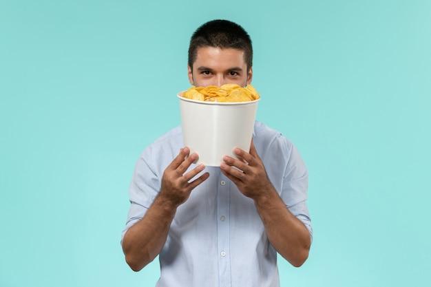 Widok z przodu młody człowiek trzyma kosz z cips i uśmiecha się na niebieskiej ścianie film zdalny film kino mężczyzna