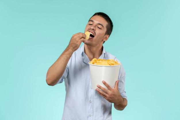 Widok z przodu młody człowiek trzyma kosz z cipsami jedzenie na niebieskiej ścianie film zdalny film kino mężczyzna