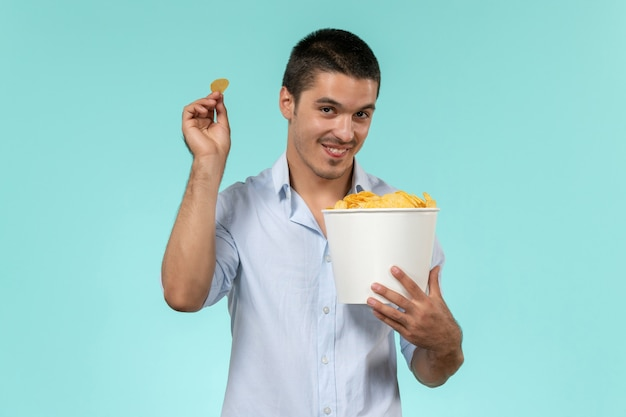 Widok z przodu młody człowiek trzyma kosz z cipsami na jasnoniebieskiej ścianie film zdalny mężczyzna kino film