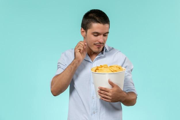 Widok z przodu młody człowiek trzyma kosz z cipsami na niebieskiej ścianie film zdalny film kino mężczyzna