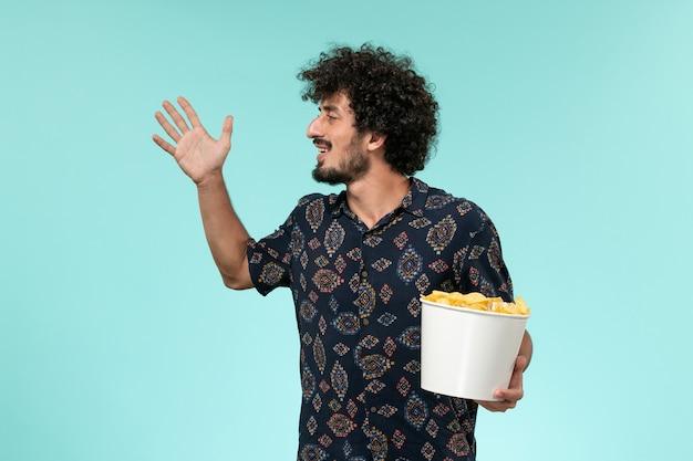 Widok z przodu młody człowiek trzyma kosz z cipsami na niebieskiej ścianie zdalnego filmu kinowego