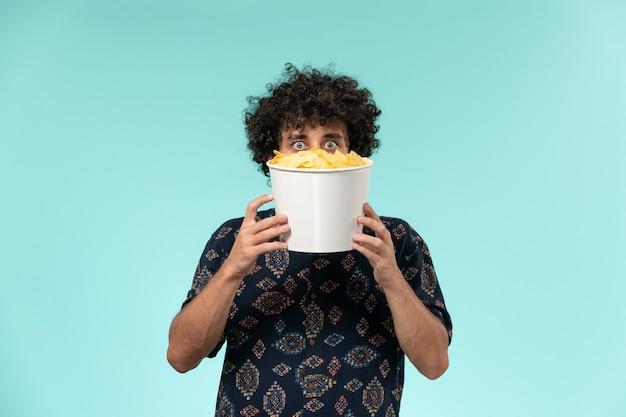 Widok z przodu młody człowiek trzyma kosz z ziemniaczanymi kipsami na niebieskiej powierzchni kino kino film teatr mężczyzna