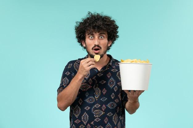 Widok z przodu młody człowiek trzyma kosz z ziemniakami i jedzenie na jasnoniebieskiej ścianie kino kino kino mężczyzna