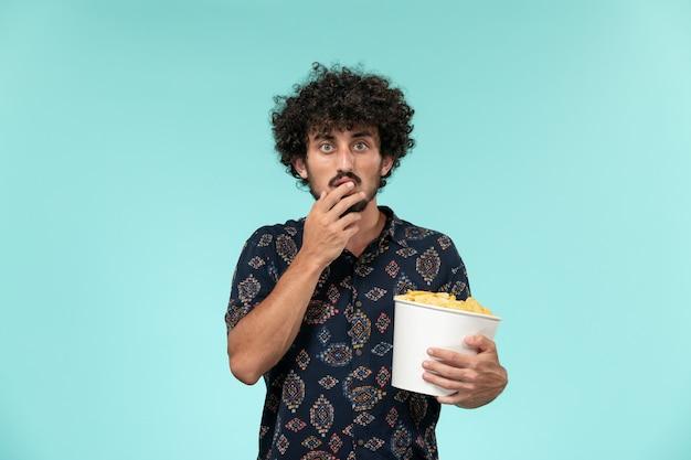 Widok z przodu młody człowiek trzyma kosz z ziemniakami i ogląda film na niebieskiej ścianie filmowe kino męskie kino teatralne