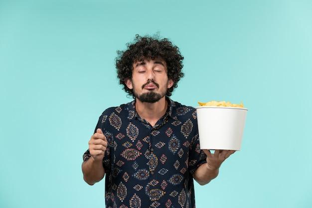 Widok z przodu młody człowiek trzyma kosz z ziemniakami i ogląda film na niebieskiej ścianie kino kino kino kino mężczyzna
