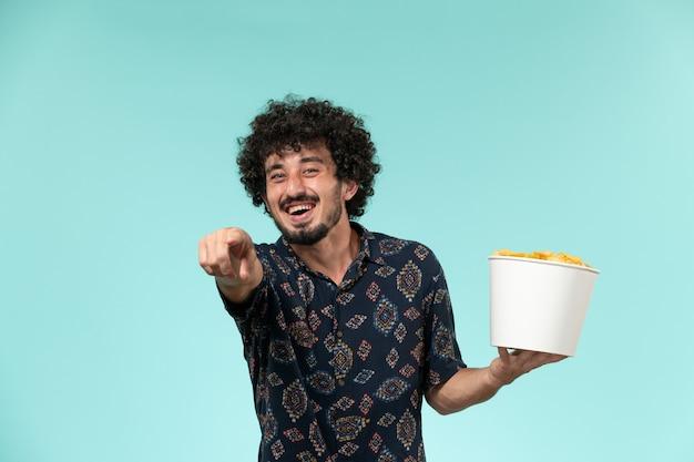 Widok z przodu młody człowiek trzyma kosz z ziemniakami i śmiejąc się głośno na niebieskiej ścianie zdalnego kina kina kina