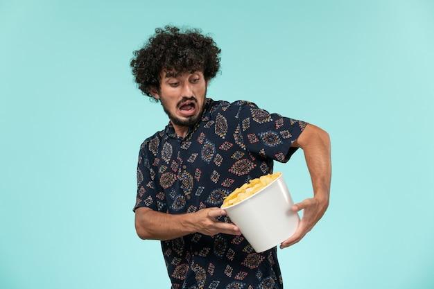 Widok z przodu młody człowiek trzyma kosz z ziemniakami na niebieskiej ścianie zdalne kino kino