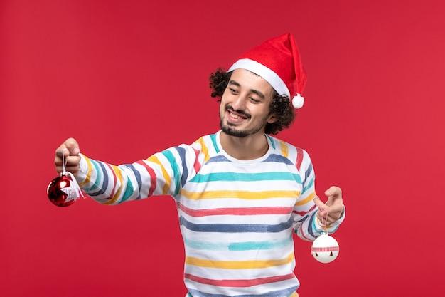 Widok z przodu młody człowiek trzyma zabawki choinkowe na czerwonej ścianie nowy rok czerwony wakacje człowieka