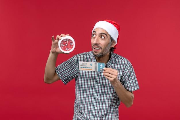Widok z przodu młody człowiek trzyma zegar i bilet na czerwonej ścianie czerwony mężczyzna emocje czas