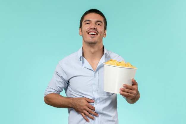 Widok z przodu młody człowiek trzyma żetony ziemniaczane na niebieskiej podłodze samotny zdalny męski kino filmowe