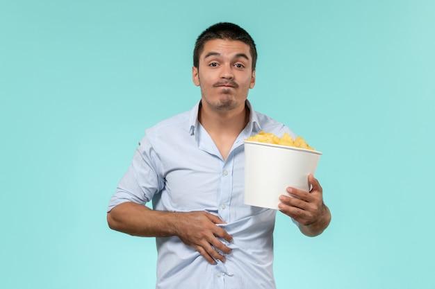 Widok z przodu młody człowiek trzymający kipsy ziemniaczane na jasnoniebieskiej ścianie samotny zdalny męski film kino