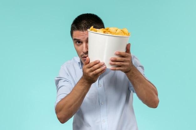 Widok z przodu młody człowiek trzymający ziemniaki podczas oglądania filmu na jasnoniebieskiej ścianie samotny zdalny męski kino filmowe