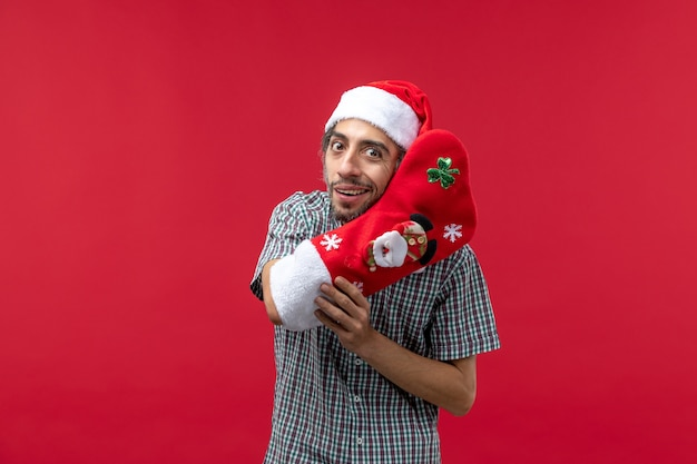 Widok z przodu młody człowiek ubrany w czerwoną skarpetę świąteczne na czerwonej ścianie