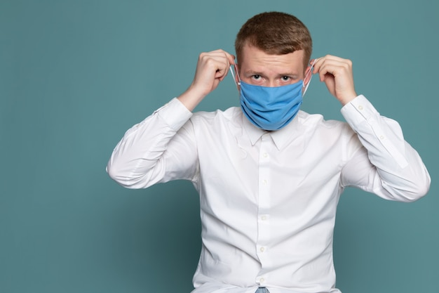 Widok z przodu młody człowiek ubrany w niebieską maskę w białej koszuli na niebieskim biurku