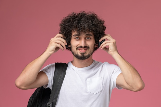Widok z przodu młody człowiek uśmiecha się i słucha piosenki pop