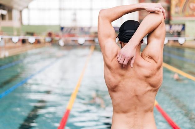 Widok z przodu młody człowiek w basenie rozciągania