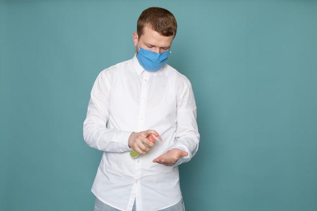 Widok z przodu młody człowiek w białej koszuli i niebieskich rękawiczkach na niebieskiej przestrzeni