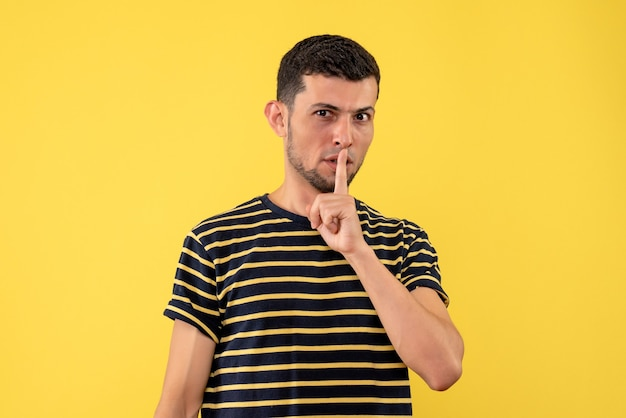 Widok z przodu młody człowiek w czarno-białe paski t-shirt co shh znak żółtym tle na białym tle