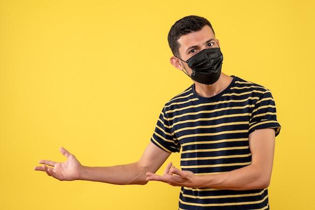 Widok z przodu młody człowiek w czarno-białe paski t-shirt na żółtym tle miejsce kopiowania