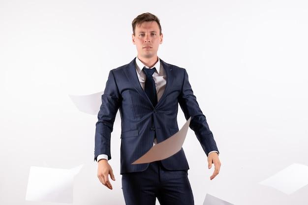 Widok z przodu młody człowiek w eleganckim klasycznym garniturze rzucający dokumenty na białym tle