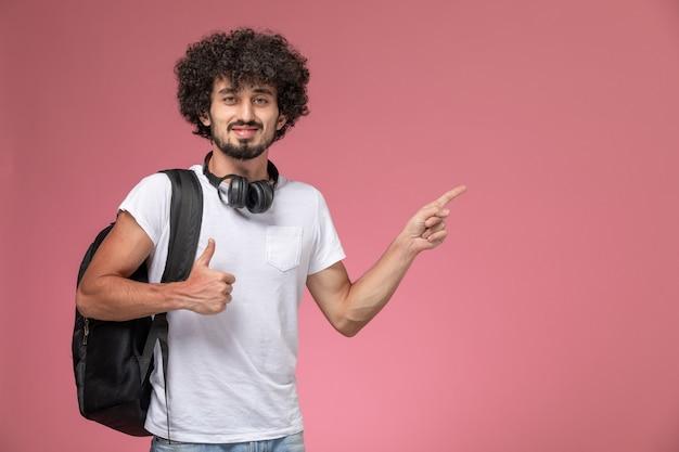 Widok z przodu młody człowiek, wskazując jego lewy kierunek z czarną torbą