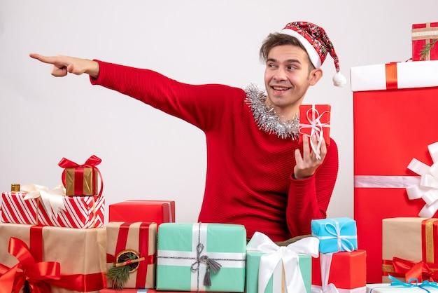 Widok z przodu młody człowiek, wskazując na coś siedzącego wokół świątecznych prezentów