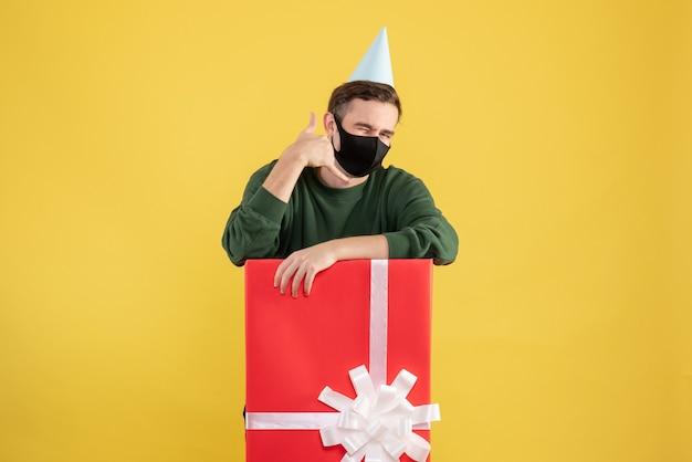 Widok z przodu młody człowiek z czapką, dzięki czemu zadzwoń do mnie znak stojący za dużym pudełkiem na prezent na żółtym tle