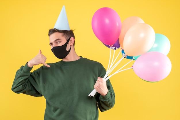 Widok z przodu młody człowiek z czapką imprezową i kolorowymi balonami, dzięki czemu zadzwoń do mnie telefon znak stojący na żółto