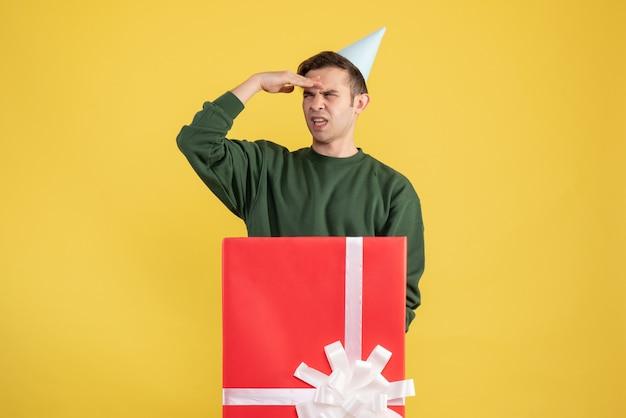 Widok z przodu młody człowiek z czapką partii patrząc na coś stojącego za dużym pudełkiem na żółtym tle