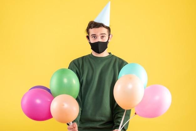 Widok z przodu młody człowiek z czapką strony, trzymając kolorowe balony stojące na żółtym tle