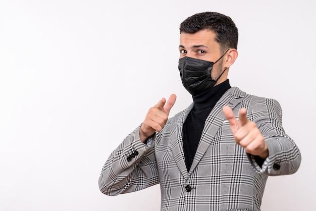 Widok z przodu młody człowiek z czarną maską, wskazując na aparat stojący na na białym tle