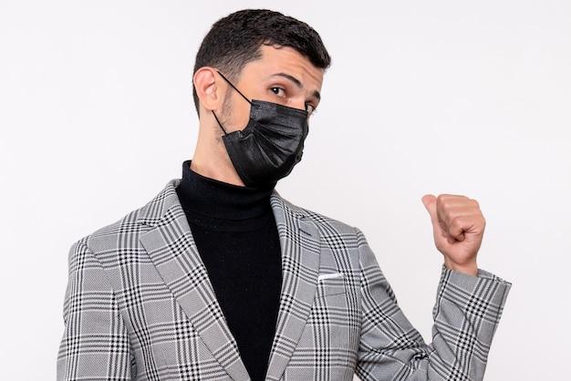 Widok z przodu młody człowiek z czarną maską, wskazując na tył stojący na na białym tle