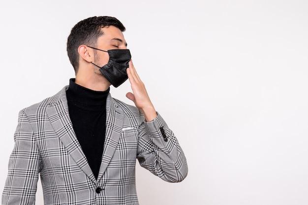 Widok z przodu młody człowiek z czarną maską zamykające oczy stojąc na na białym tle