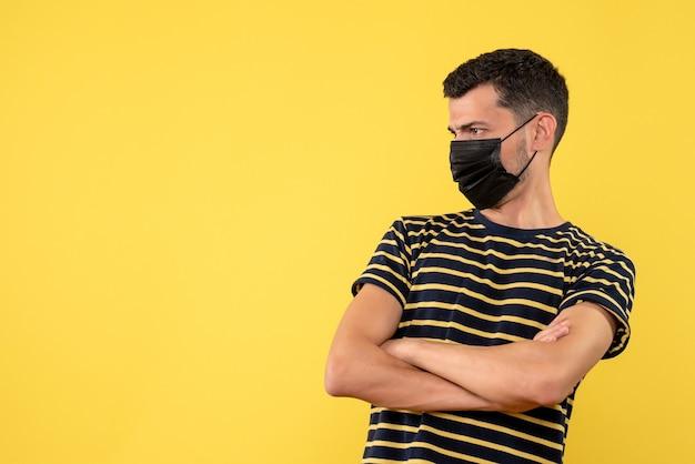 Widok z przodu młody człowiek z czarno-białą koszulką w paski skrzyżowane ręce na żółtym tle miejsce kopiowania