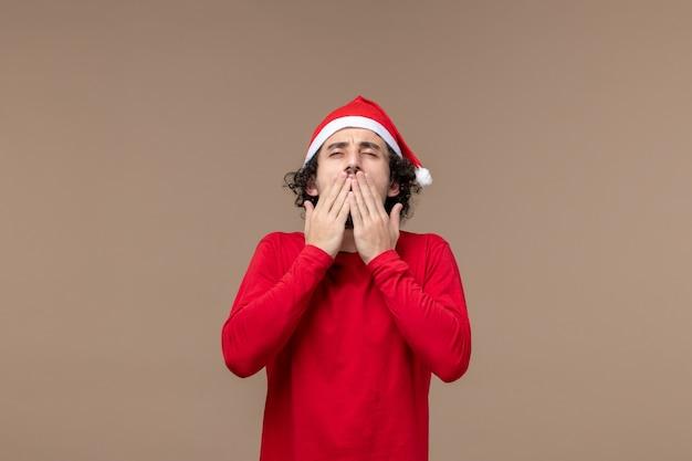 Widok z przodu młody człowiek z czerwoną peleryną boże narodzenie na brązowym tle emocje wakacje boże narodzenie