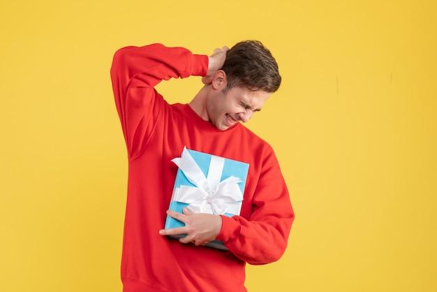 Widok z przodu młody człowiek z czerwonym swetrem, trzymając głowę na żółtym tle