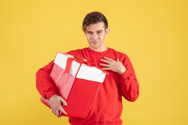 Widok z przodu młody człowiek z czerwonym swetrem, trzymając świąteczny prezent na żółtym tle