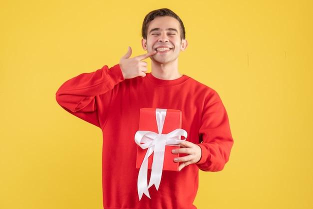 Widok z przodu młody człowiek z czerwonym szkatułce, wskazując na jego uśmiech na żółtym tle