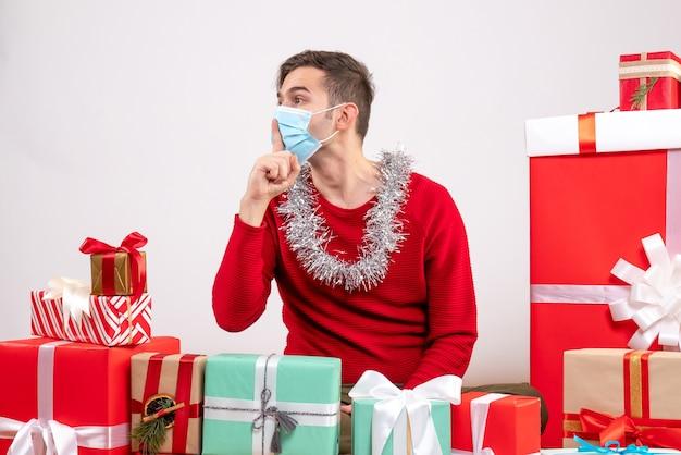 Widok z przodu młody człowiek z maską co znak shh siedzący wokół świątecznych prezentów biały