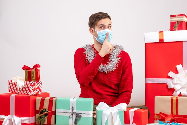 Widok z przodu młody człowiek z maską co znak shh siedzi wokół prezentów bożonarodzeniowych