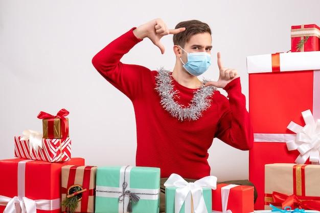 Widok z przodu młody człowiek z maską dokonywanie znaku aparatu siedzącego wokół świątecznych prezentów
