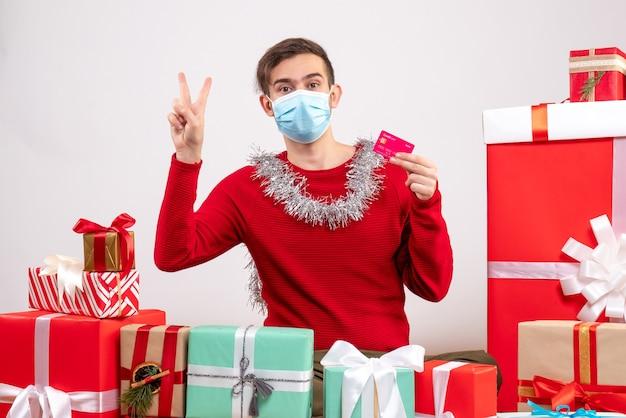 Widok z przodu młody człowiek z maską, dzięki czemu znak pokoju zwycięstwa siedzi wokół świątecznych prezentów