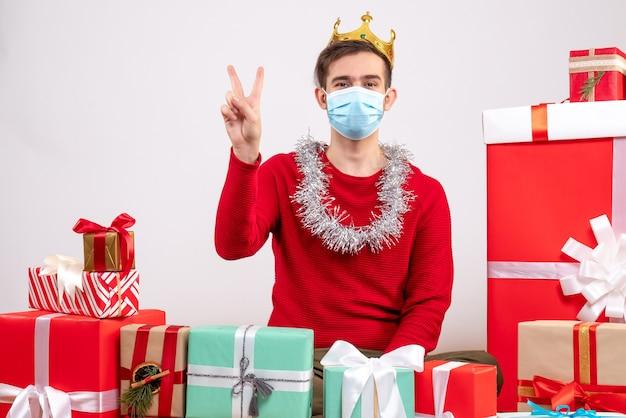 Widok z przodu młody człowiek z maską, dzięki czemu znak zwycięstwa siedzi na podłodze wokół świątecznych prezentów