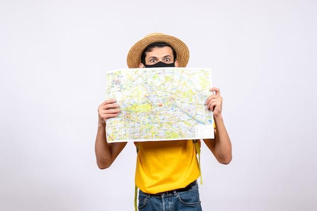 Widok z przodu młody człowiek z maską i żółtą koszulką przedstawiającą mapę